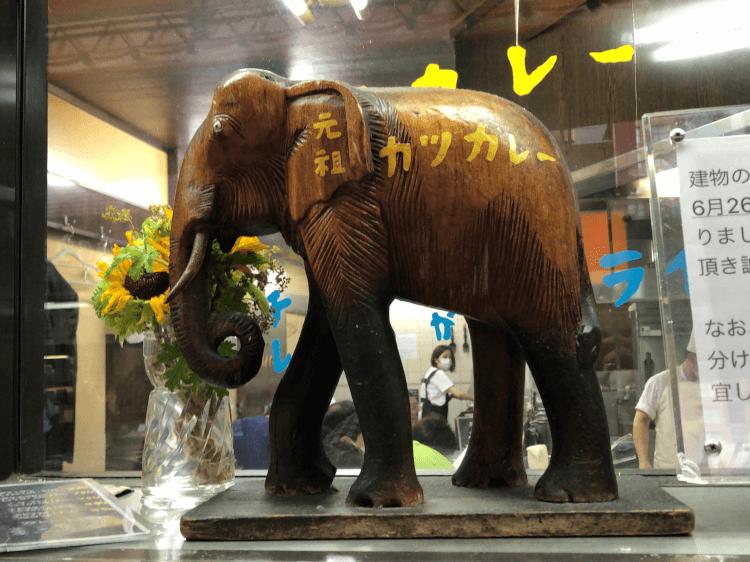 元祖カツカレーと書かれた木彫りの象