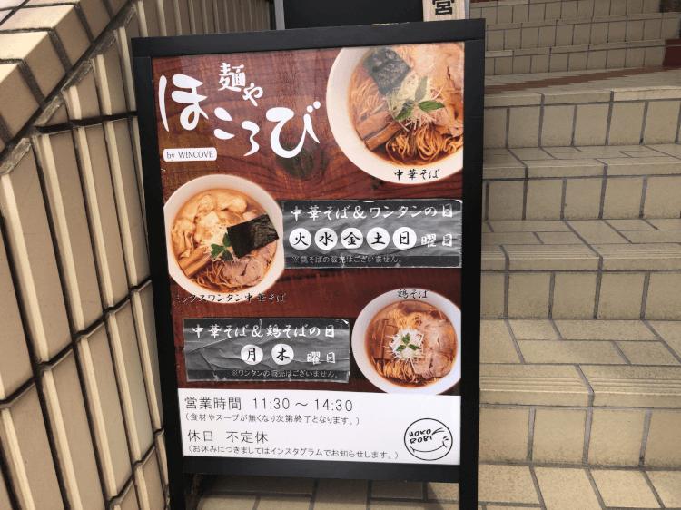 途中の階段に置かれた麺やほころびの看板